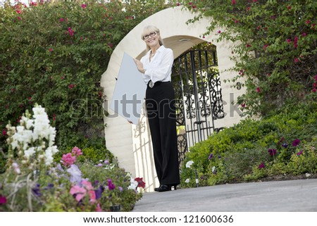 Senior female real estate agent holding sign board in front of entrance gate - stock photo
