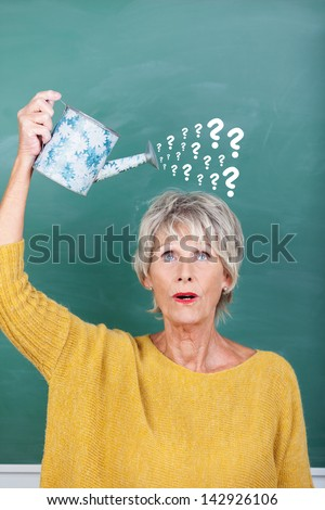 Senior female teacher holding watering can with question marks on chalkboard representing confusion - stock photo