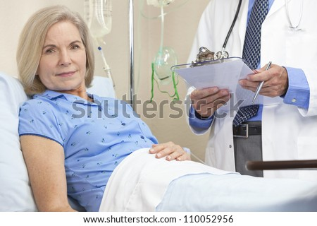 Senior female woman patient in a hospital bed being cared for by a male nurse or doctor - stock photo