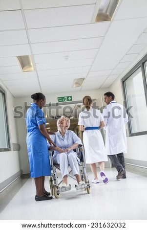 Senior female woman patient in wheelchair sitting in hospital corridor with African American female nurse and Asian doctor - stock photo