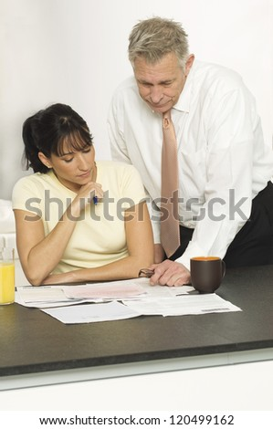 Senior financial adviser with female client reading documents in office