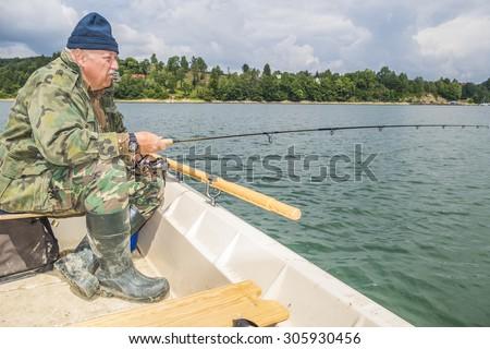 Senior fisherman fishing on Solina Lake in Poland - stock photo
