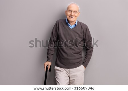 Senior gentleman holding a black cane and leaning against a gray wall - stock photo