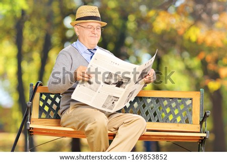 Senior gentleman seated on a bench reading a newspaper in a park - stock photo