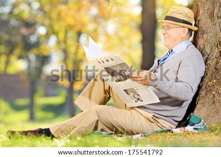 Senior gentleman seated on a grass reading newspaper in a park at autumn - stock photo