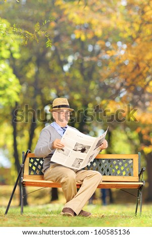 Senior gentleman seated on a wooden bench reading a newspaper in a park at autumn - stock photo