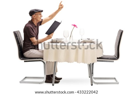 Senior gentleman sitting at a restaurant table and calling the waiter isolated on white background - stock photo