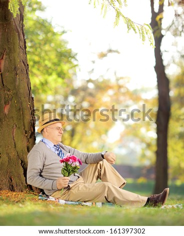 Senior gentleman with bunch of flowers sitting on a green grass and checking the time, in a park, shot with a tilt and shift lens