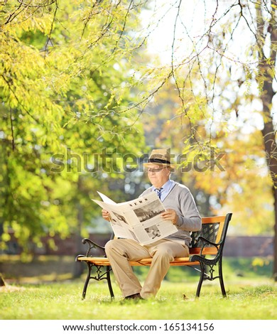 Senior gentleman with hat sitting on a wooden bench and reading a newspaper in a park, shot with tilt and shift - stock photo