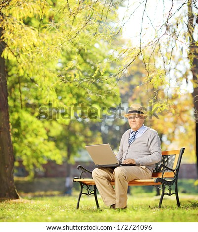 Senior gentleman working on laptop seated on bench in park looking at camera, shot with a tilt and shift lens - stock photo