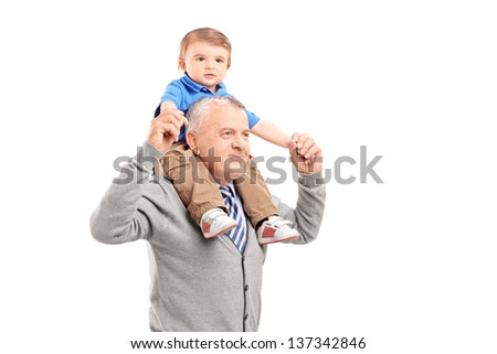 Senior giving a piggy back ride to his grandson isolated on white background - stock photo