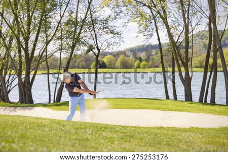 Senior golf player hitting ball in bunker, with lake and trees in background. - stock photo
