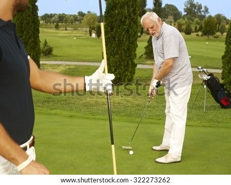 Senior golfer standing on the green ready for holing. - stock photo