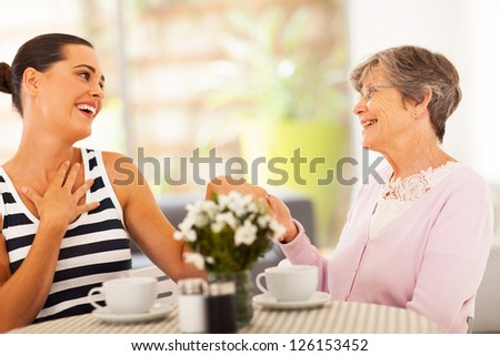senior grandmother looking at granddaughter's new ring - stock photo
