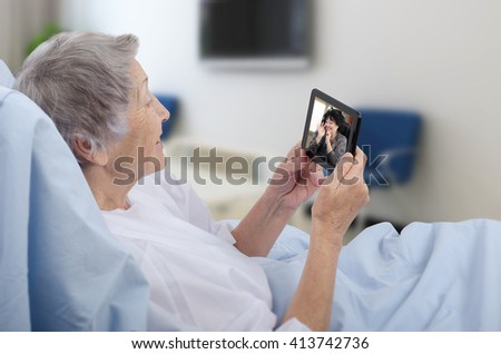 Senior grey-haired female patient lying on hospital bed has video chat with happy woman on small digital tablet. This hospital offers free wireless internet access Wi-Fi. - stock photo