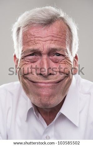 Senior grinning from ear to ear. Humorous portrait of a retired gray haired senior man with a wide beaming smile that epitomises the idiom, grinning from ear to ear - stock photo