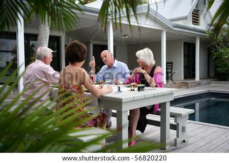 Senior group having a dinner on a terrace near a swimming pool - stock photo