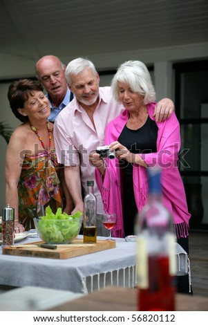 Senior group watching photos on a digital camera - stock photo