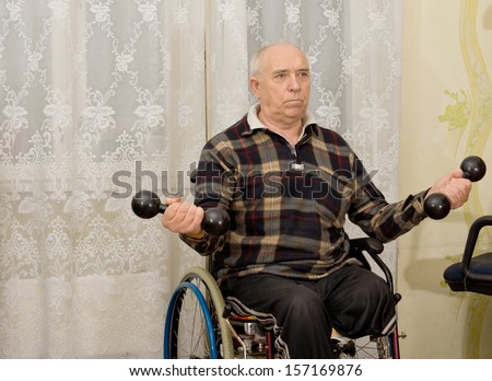Senior handicapped male amputee sitting in his wheelchair doing exercises working out with a pair of dumbbells - stock photo