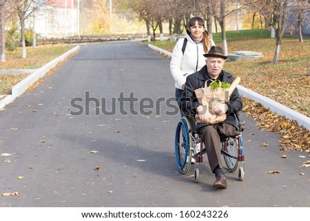 Senior handicapped man with a female carer being pushed along the street in his wheelchair as he holds a bag of groceries on his lap