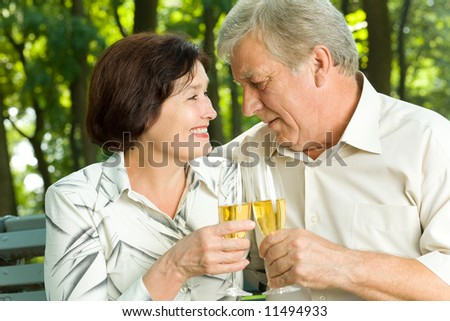 Senior happy couple celebrating with champagne outdoors