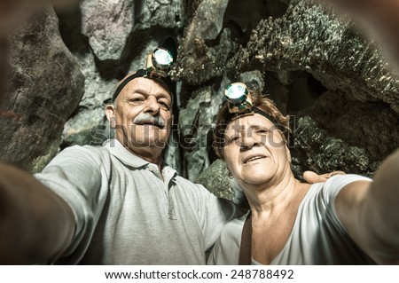 Senior happy couple taking a selfie at the entrance of Tham Phu Kham in Vang Vieng - Adventure travel in Laos and asian destinations - Concept of active elderly around the world with new technologies - stock photo