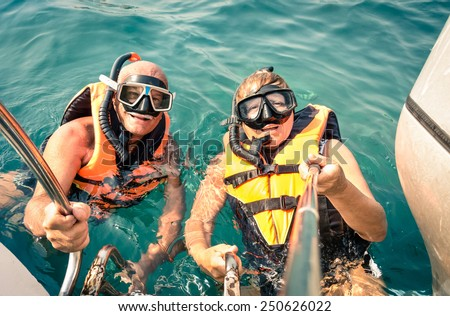 Senior happy couple using selfie stick in tropical sea excursion - Boat trip snorkeling in exotic scenarios - Concept of active elderly and fun around the world - Soft vintage filtered look - stock photo