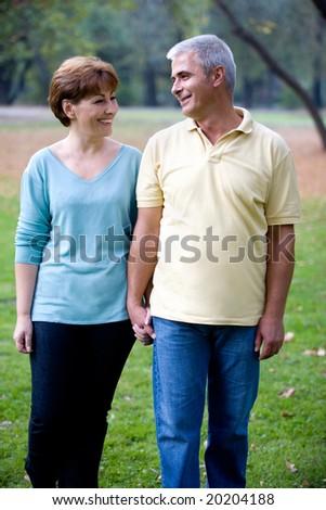 senior happy couple walking at the park - stock photo