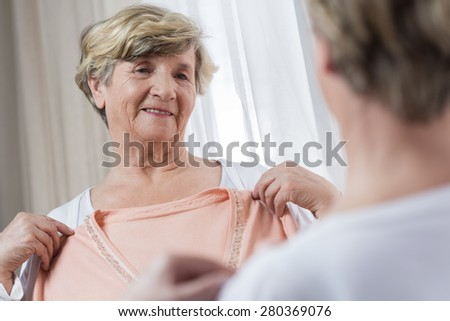 Senior happy elegant woman choosing dress in front the mirror - stock photo