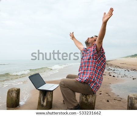 Senior happy man sitting at the beach with laptop on a foggy day