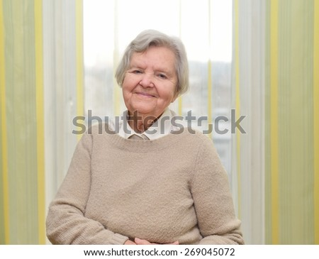 Senior happy woman in her home with window on background. MANY OTHER PHOTOS FROM THIS SERIES IN MY PORTFOLIO.  - stock photo
