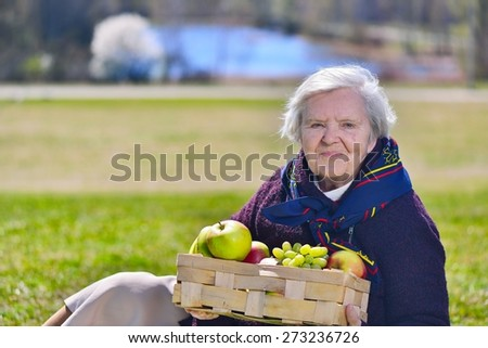Senior happy woman sitting on on glade in the park. Healthy outdoor activities. Happy and smiling. MANY OTHER PHOTOS FROM THIS SERIES IN MY PORTFOLIO.  - stock photo
