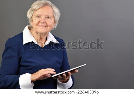 Senior happy woman with tablet against grey background. - stock photo