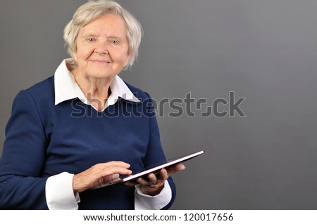 Senior happy woman with tablet against grey background. MANY OTHER PHOTOS WITH THIS SENIOR MODEL IN MY PORTFOLIO. - stock photo