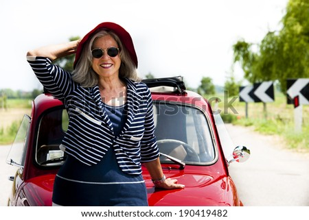 Senior happy woman with vintage car - stock photo