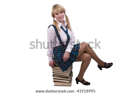 Senior high school student in uniform with documents is sitting on the stack of book. A young and beautiful schoolgirl  is wearing a traditional uniform with textbooks. - stock photo