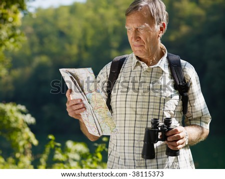 senior hiker holding map and binoculars. Copy space - stock photo