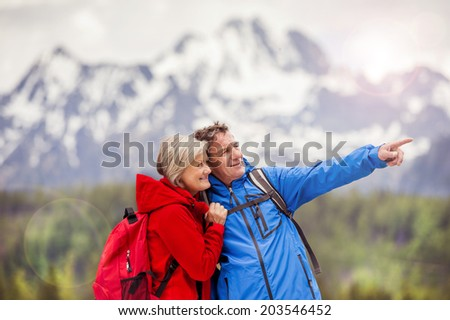 Senior hikers couple during the walk in beautiful mountains, hills and hotel in background - stock photo
