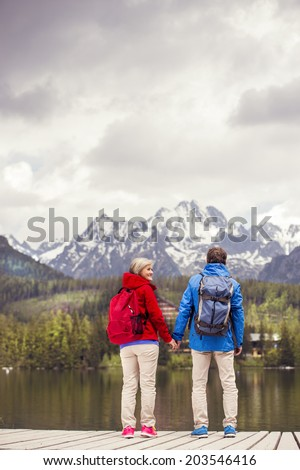 Senior hikers couple during the walk round the tarn in beautiful mountains, hills and hotel in background - stock photo