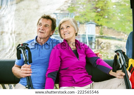 Senior hikers couple going up the mountain by cableway - stock photo