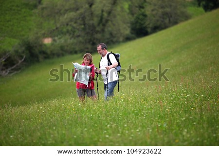 Senior hikers reading map in country field - stock photo