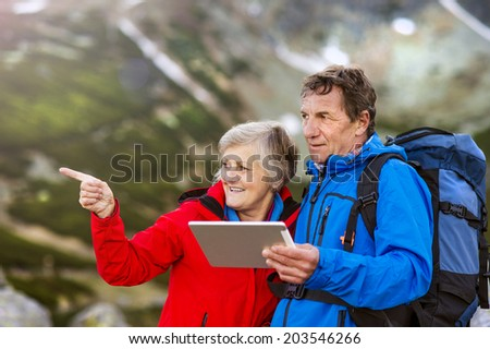 Senior hiking couple using travel app or map on tablet during the hike. - stock photo