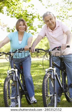Senior Hispanic Couple Cycling In Park