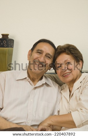 Senior Hispanic couple hugging and smiling indoors - stock photo