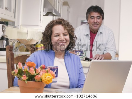 Senior Hispanic couple relaxing in kitchen
