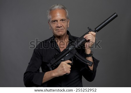 senior hit man with automatic rifle with silencer on grey background - stock photo