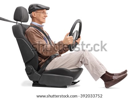 Senior holding a steering wheel seated on a car seat fastened with seatbelt isolated on white background - stock photo