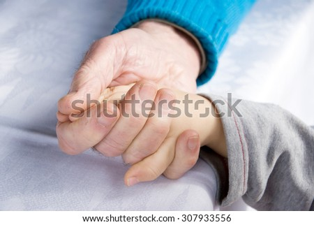 senior holding the hand of a young child - stock photo