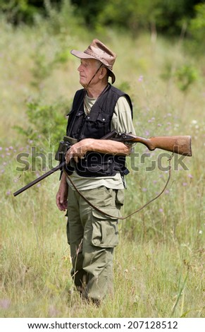 Senior hunter with shotgun and binoculars walking in forest - stock photo