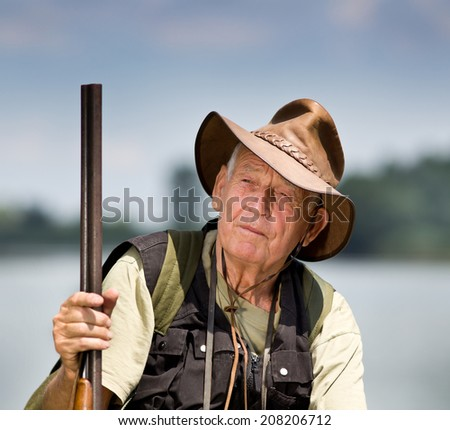 Senior hunter with shotgun sitting beside lake - stock photo